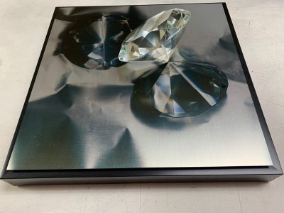 """Connie Zehr • <em>Image and Object II</em> • Assemblage: metal print with large, round, gem-cut glass object • 12""""×12""""×3"""" • $50.00<a class=""""purchase"""" href=""""https://state-of-the-art-gallery.square.site/product/connie-zehr-image-object-ii/530"""" target=""""_blank"""">Buy</a>"""